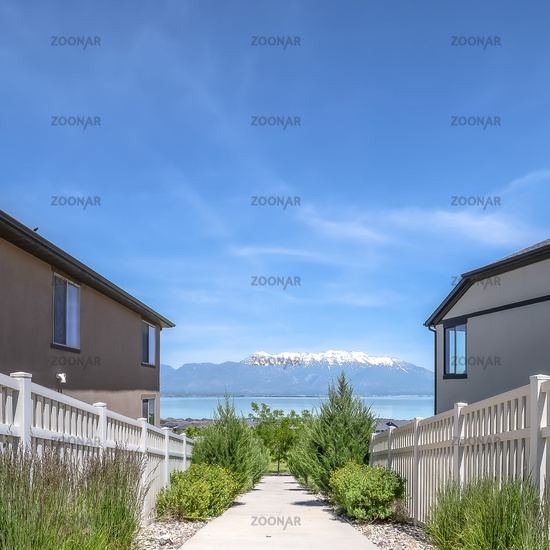Square Walkway in the middle of homes with lake snow peaked mountain and sky view