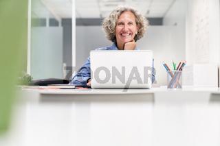 Glückliche Seniorin beim E-Learning am Computer