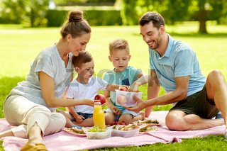 happy family having picnic at summer park