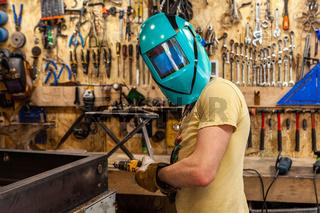 Metalworker wears protective mask