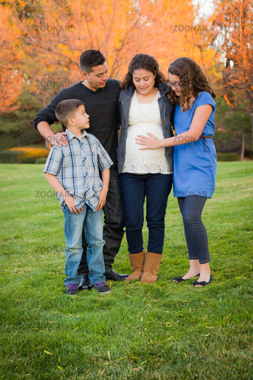 Hispanic Pregnant Family Portrait Against Fall Colored Trees
