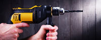Male hands holding power drill.
