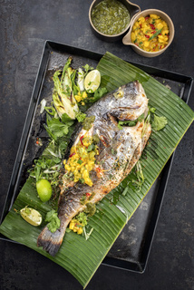 Fresh barbecue gilthead seabream with lettuce and mango chutney as top view on a green banana leaf