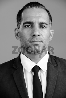 Face of mature handsome Persian businessman in black and white