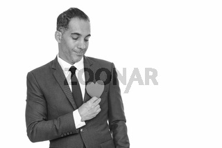 Mature handsome Persian businessman holding red heart ready for Valentine's day