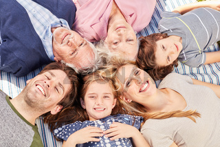 Familie mit Großeltern liegt zusammen im Kreis