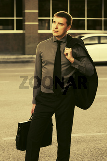 Young hansome business man wearing black suit walking in city street