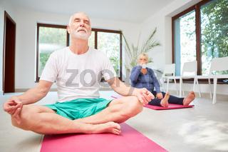 Senior meditiert mit geschlossenen Augen
