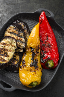 Barbecue eggplant and paprika as side dish at a summer party as top view a cast iron design plate
