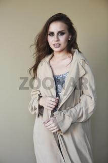 Beautiful young fashion model wearing a trench coat