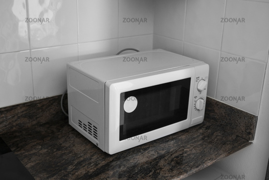 Microwave in a kitchen for cooking or heating a dish.