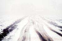 Winter foggy road among fields in December.