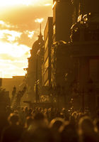 Crowd of people walking down the street at summer evening, beautiful light at sunset