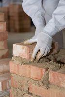Handwerker mauert Ziegelwand mit kleinen Ziegelsteinen - Nahaufnahme Maurer