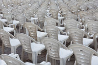 White plastic chairs in row stand waiting for visitors