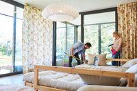 Junges Paar beim Frühjahrsputz im Wohnzimmer