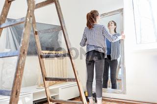 Junge Frau hängt einen Spiegel an die Wand