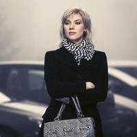 Fashion blond woman in black coat with hanbag walking in city street