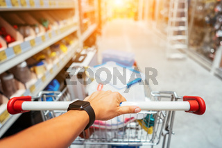 Human Hand Close Up With Shopping Cart in a Supermarket Walking Trough the Aisle