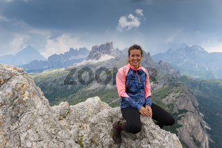 attractive brunette mountain climber sitting on a mountain peak and smiling