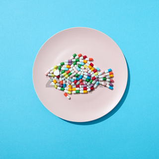 Fish from colorful pills and tablets on a white plate on a blue background with copy space. Colorful food supplement pills. Top view.