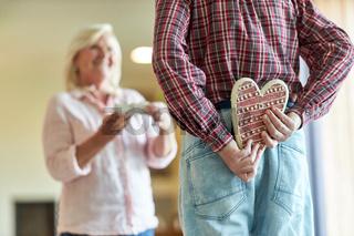 Senior versteckt ein Lebkuchen Herz als Geschenk