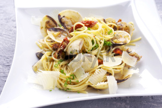 Spaghetti alle vongole with tomato pesto as close-up on a plate