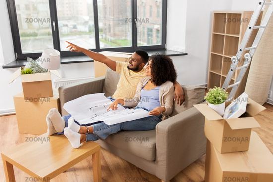 couple with boxes and blueprint moving to new home