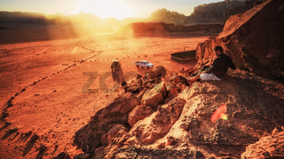 Couple Sitting Together on Desert Valley Landscape Sunset Orange Red Travel Adventure Exotic Location Rocky Cliff