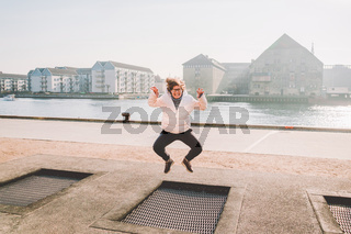 adult person rejoices like child. Playground trampoline in ground, children trampoline, springs throws people up fun and cool. Copenhagen River Embankment Denmark. Woman jumping on street trampoline