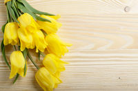 Bouquet of yellow tulips on natural wooden background with space for text