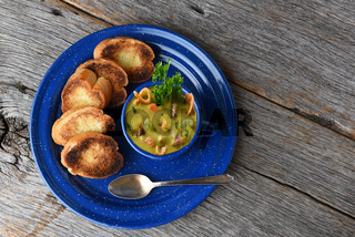 Split Pea soup with garlic toast on a rustic wood table with copy space.