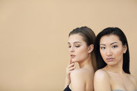 Two beautiful multicultural young women hugging while posing camera