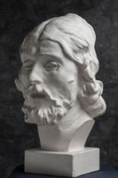 Gypsum copy of ancient statue John the Baptist head on dark textured background. Plaster sculpture man face.