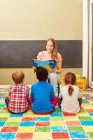 Kindergärtnerin beim Vorlesen im Kindergarten