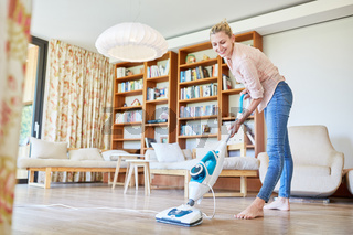 Putzfrau mit Dampfreiniger im Wohnzimmer