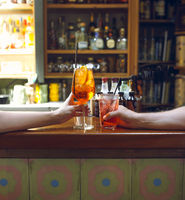 Woman and man raising a glasses of coktails