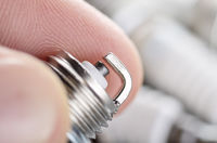 Closeup photo of new spark plug for internal combustion engine in human hand. Space for text