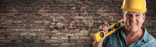 Male Contractor In Hard Hat Holding Level In Front Of Old Brick Wall Banner with Copy Space