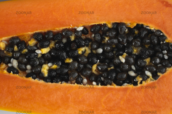 Half cut ripe papaya with seed on a white plate. Slices of sweet papaya with a white background. Halved papayas. Healthy exotic fruits. Vegetarian food.