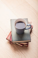 A few books with cup of coffee on wooden floor