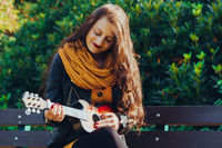 Attractive young woman musician in a fall park