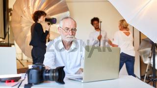 Älterer Fotograf bei Bildbearbeitung am Computer