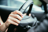 Sports car steering wheel, hands of a young girl with purple nail polish