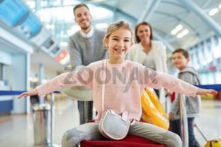 Glückliches Mädchen und Familie im Flughafen