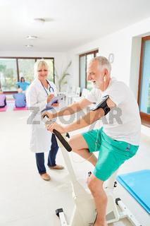 Senior Mann trainiert auf dem Ergometer