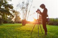 Frau mit Kamera auf dem Stativ als Naturfotografin