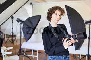 Junge Frau als selbständige Fotografin mit Kamera
