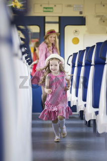 Cheerful little girl runs away from her mother at the train
