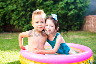 Theme is a children's summer vacation. Two Caucasian children, brother and sister, sit in a perched round pool with water in the yard of the green grass in a bathing suit and joy happiness smile